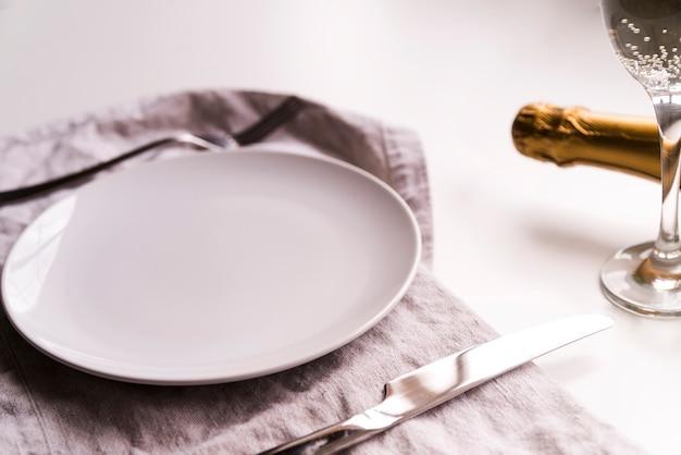 Lege plaat met botermes op servet dichtbij champagnefles over witte achtergrond Gratis Foto