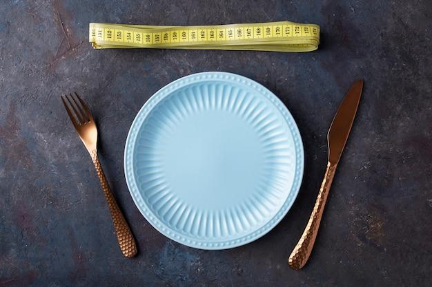 Lege plaat met vork en mes in de buurt van meetlint. dieet voor gewichtsverlies concept. bovenaanzicht Premium Foto