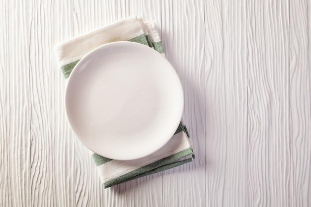 Lege plaat op geruit tafelkleed op witte houten lijst Premium Foto