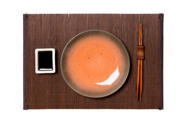 Lege ronde bruine plaat met eetstokjes voor sushi en sojasaus op donkere bamboemat Premium Foto
