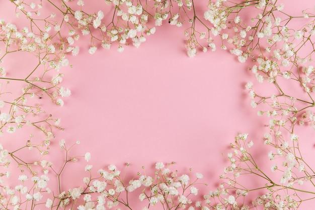 Lege ruimte voor het schrijven van tekst met verse witte gypsophila bloem tegen roze achtergrond Gratis Foto