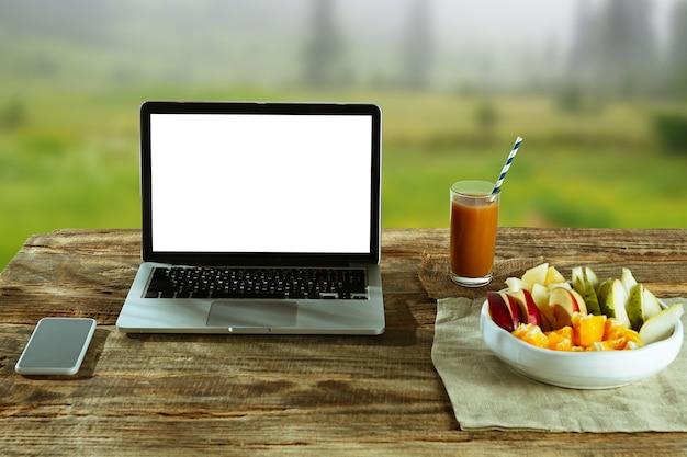 Lege schermen van laptop en smartphone op een houten tafel buiten met natuur op muur fruit en vers sap in de buurt. concept van creatieve werkplek, zaken, freelance. copyspace. Gratis Foto