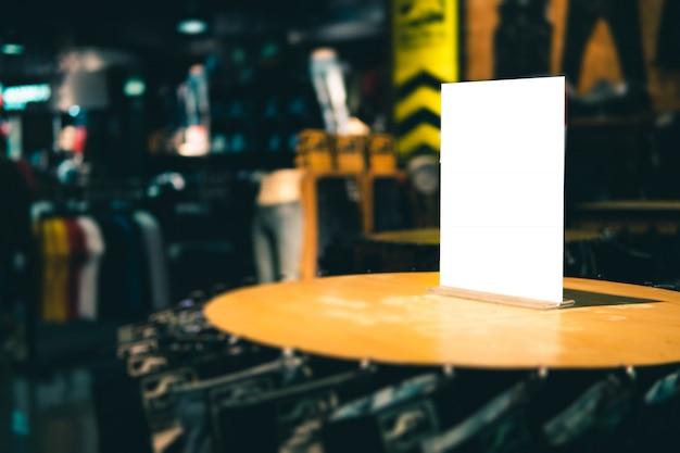 Lege sjabloon van de etiketribune op schort in kledingsopslag of opslag voor voor verkoopbevordering en kortingsinformatie op. Premium Foto