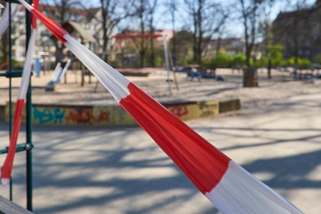 Lege speeltuin zonder kinderen, gesloten voor kinderen en ouders. knip af met gestreepte rood-witte waarschuwingstape. Premium Foto