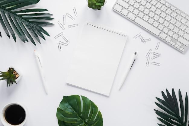 Lege spiraalvormige blocnote met toetsenbord; paperclips en groene bladeren op witte achtergrond Gratis Foto