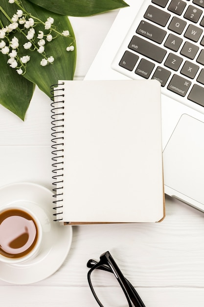 Lege spiraalvormige blocnote op laptop en koffiekop met bladeren en bloemen op bureau Gratis Foto
