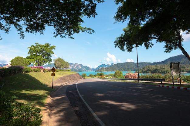 Lege straat bij de mooie en comfortabele grote tuin onder mooie blauwe hemel Premium Foto