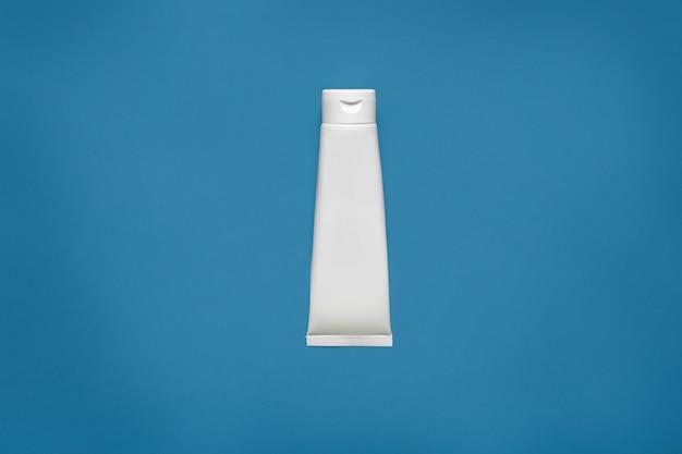 Lege witte buis ontwerp mockup geïsoleerd op blauw, uitknippad. doorzichtige crème verpakking, mock up. lotion huidverzorging lege pakketcontainer. scincare, cosmetisch concept. gel, tube, flacon. Gratis Foto