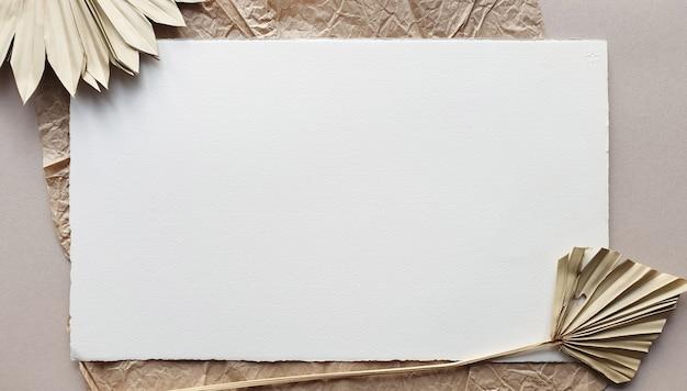 Lege witte de uitnodigingskaartenmodellen van het huwelijk met droog palmblad op geweven lijst backgound. elegante moderne sjabloon voor branding identiteit. tropisch ontwerp. plat lag, bovenaanzicht Premium Foto
