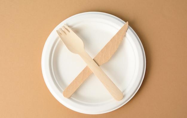 Lege witte papieren plaat en houten mes en vork, objecten gekruist, bovenaanzicht Premium Foto