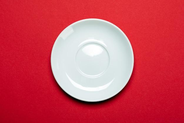 Lege witte plaat die op rode oppervlakte wordt geïsoleerd Premium Foto
