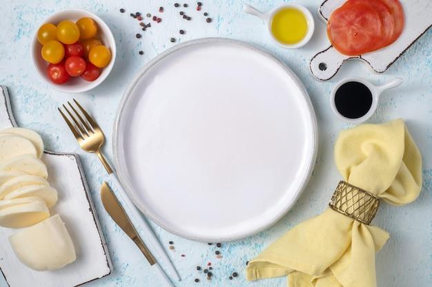 Lege witte plaat omgeven door bestek en verse groenten bovenaanzicht op blauwe achtergrond Premium Foto