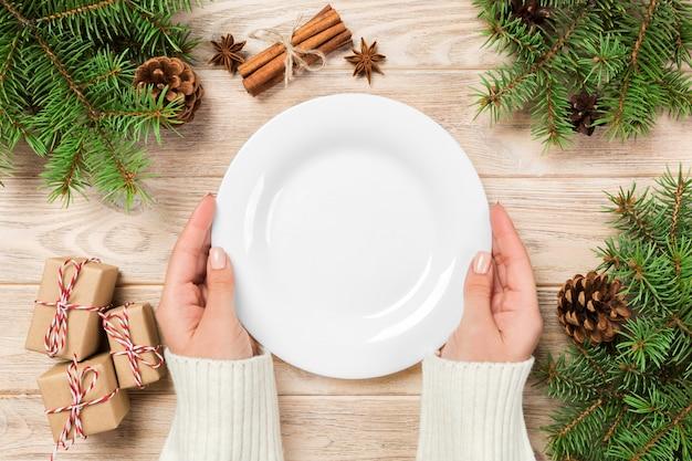 Lege witte plaat op houten oppervlak met kerstdecoratie Premium Foto
