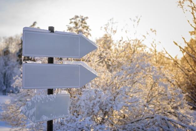 Lege witte trackpointers, wegwijzer in zonlicht tegen winteraard. directionele pijltekens op houten paal in besneeuwd bos. Premium Foto