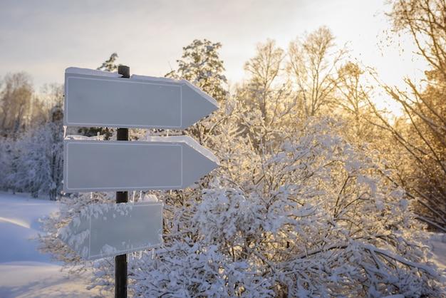 Lege witte trackpointers, wegwijzer in zonlicht tegen winteraard Premium Foto