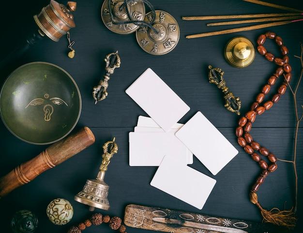 Lege witte visitekaartjes in het midden van aziatische religieuze objecten voor meditationnd alternatieve geneeskunde Premium Foto