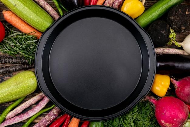 Lege zwarte pan met verse groenten rond Gratis Foto