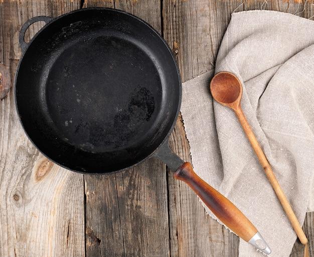 Lege zwarte ronde koekenpan met handvat en lepel Premium Foto