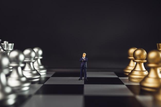 Leidersminiatuur temidden van team- of personeelsconcept. werkgever die zich voor gouden schaak op schaakbord bevindt met weinig licht. Premium Foto