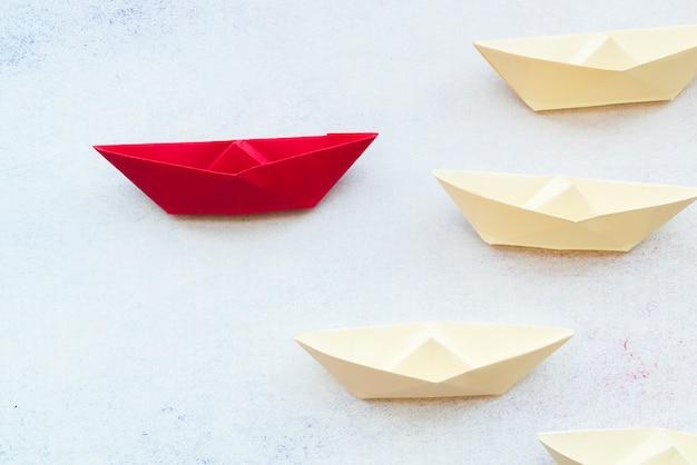 Leidingsconcept die rood document schip onder wit op achtergrond gebruiken Gratis Foto