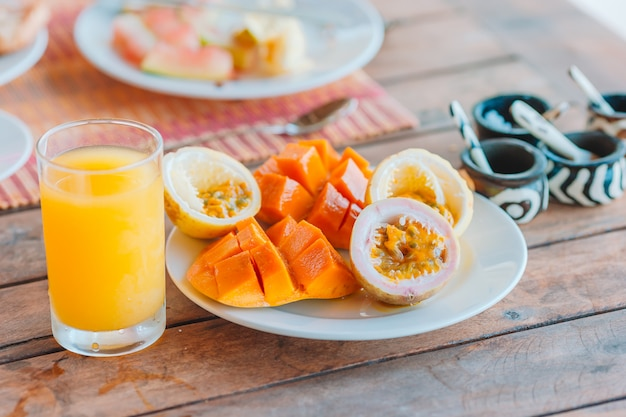 Lekker exotisch fruit - rijp passievrucht, mango bij het ontbijt bij restaurant buiten Premium Foto