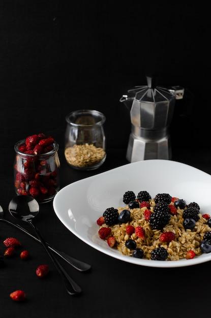 Lekker gezond ontbijt. havermoutpap met wilde bessen op donkere achtergrond. Premium Foto