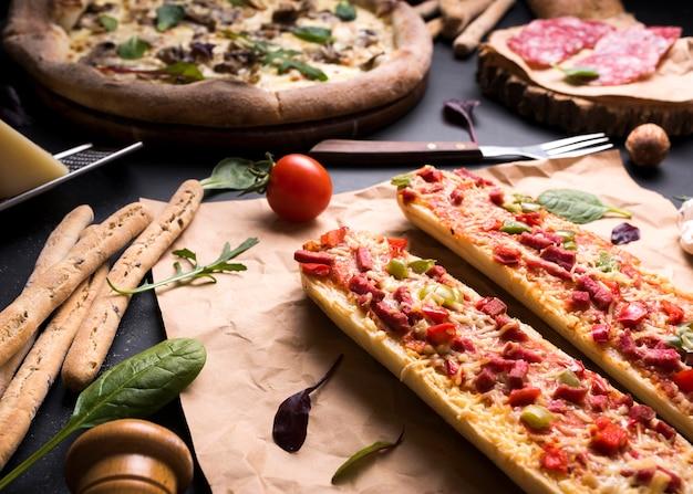 Lekker italiaans eten met kerstomaatjes; broodstokken en vork Gratis Foto