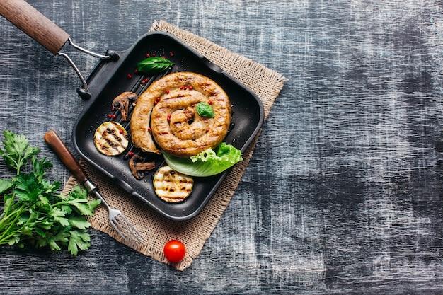 Lekkere geroosterde spiraalvormige worsten voor maaltijd op grijze houten achtergrond Gratis Foto