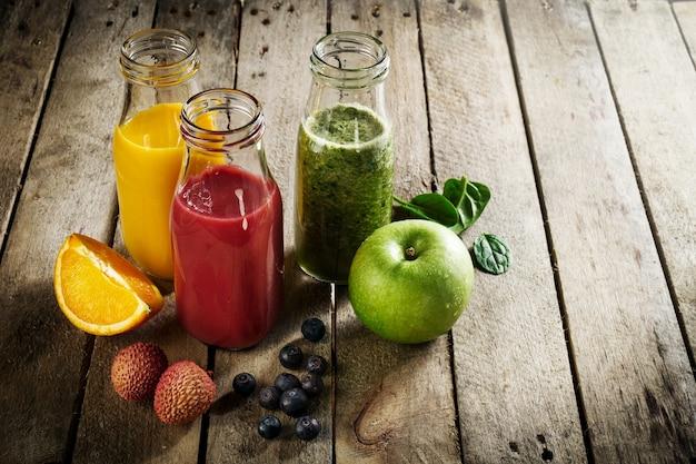 Lekkere, kleurrijke, verse zelfgemaakte smoothies in glazen potjes op houten tafel. gezond, detox concept. Gratis Foto