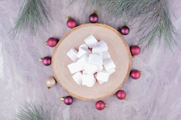 Lekkere marshmallows op een houten bord met rond eikenboomballen Gratis Foto