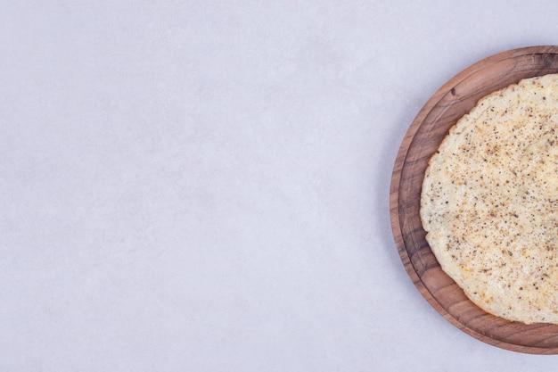 Lekkere pizza op houten plaat op wit oppervlak Gratis Foto