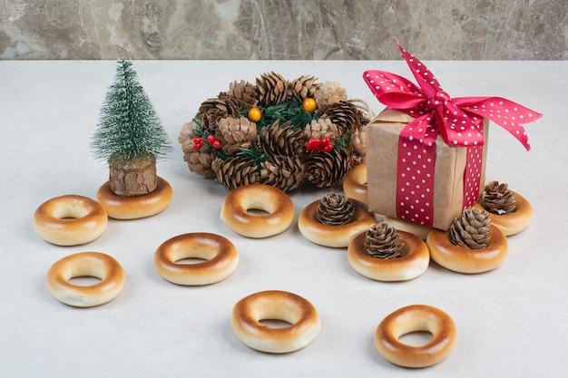 Lekkere ronde koekjes met dennenappels en geschenkdoos op witte achtergrond. hoge kwaliteit foto Gratis Foto