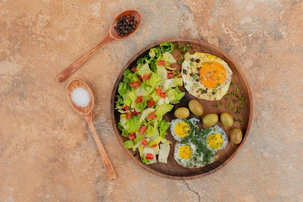 Lekkere salade met eieren op een houten bord. Gratis Foto
