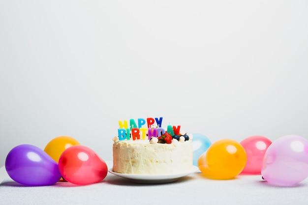Lekkere taart met bessen en gelukkige verjaardagstitel in de buurt van ballonnen Premium Foto