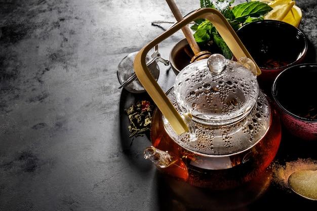Lekkere verse groene thee in glazen theepot ceremonie op donkere achtergrond hierboven Gratis Foto