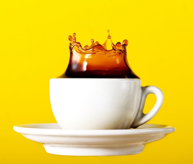 Lekkere verse zwarte koffie in kopje plons kroon op gele levendige achtergrond. kunst ontwerp Gratis Foto