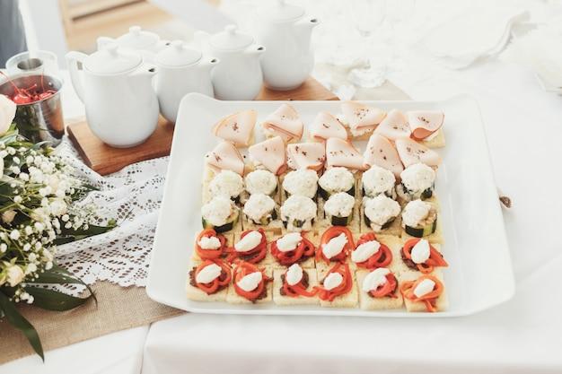 Lekkere voorgerechten van vis en groenten geserveerd op vierkante