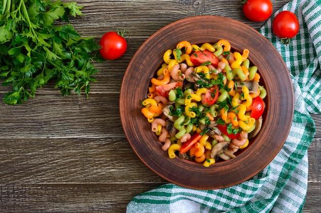 Lekkere warme salade. gekleurde pasta met champignons en verse tomaten in een kom op een houten tafel. pasta colorata. het bovenaanzicht Premium Foto