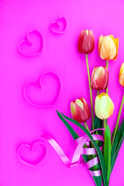 Lente bloem van meerdere kleuren tulpen op roze achtergrond, flat lag afbeelding voor vakantie wenskaart voor moederdag, valentijnsdag, vrouwendag en kopieer de spatie voor uw tekst Premium Foto