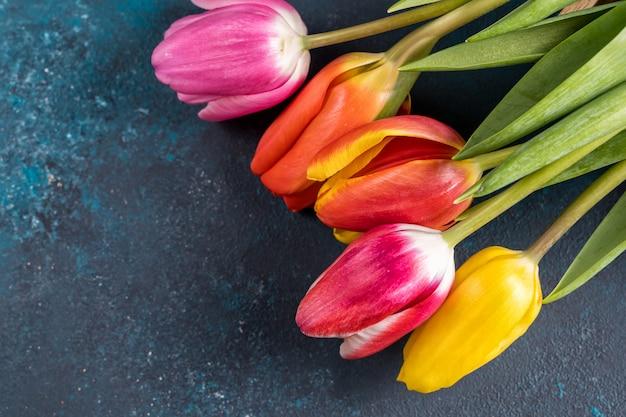 Lente bloemen boeket. mooie tulpen op rustieke heldere kleuren blauwe achtergrond. bovenaanzicht, kopieer ruimte. Premium Foto