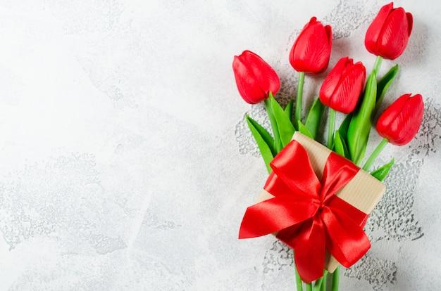 Lente boeket van rode tulpen en geschenkdoos. Premium Foto