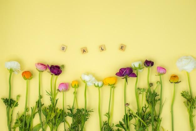 Lente flatlay concept achtergrond met bloemen en verkoop houten woord Premium Foto