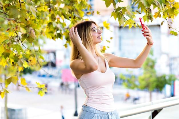 Lente levensstijl portret van mooie blonde vrouw selfie maken en spreken op videochat met haar vriend, sportieve casual kleding, zonnige pastelkleuren. Gratis Foto