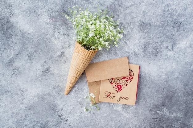 Lente minimale concept. wafelkegel met gypsophila bloemen. mother's woman day concept. Premium Foto