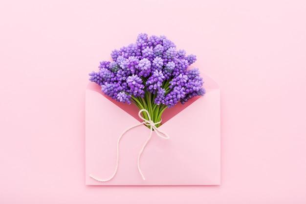 Lente paarse bloemen in roze envelop Premium Foto