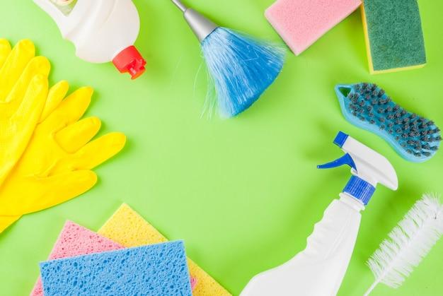 Lente schoonmaak concept met leveringen, huis schoonmaak producten stapel. het concept van het huishoudenkarwei, op groen hoogste menings copyspace kader Premium Foto