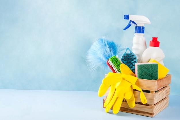 Lente schoonmaak concept met leveringen, huis schoonmaak producten stapel. het concept van het huishoudenkarwei, op lichtblauwe achtergrondexemplaarruimte Premium Foto