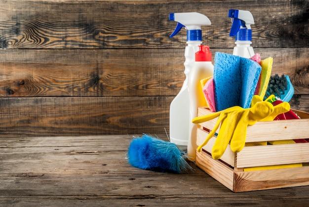 Lente schoonmaak concept met leveringen, huis schoonmaak producten stapel. het concept van het huishoudenkarwei, op plattelander of tuin houten achtergrondexemplaarruimte Premium Foto