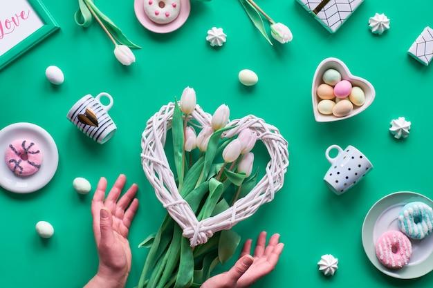 Lente verjaardag of jubileum. wattled hart, paaseieren in hart kom, koffiekopjes, verse tulpen, geschenken. geometrische lente plat lag in wit en roze op groene muur pasen, moederdag, Premium Foto