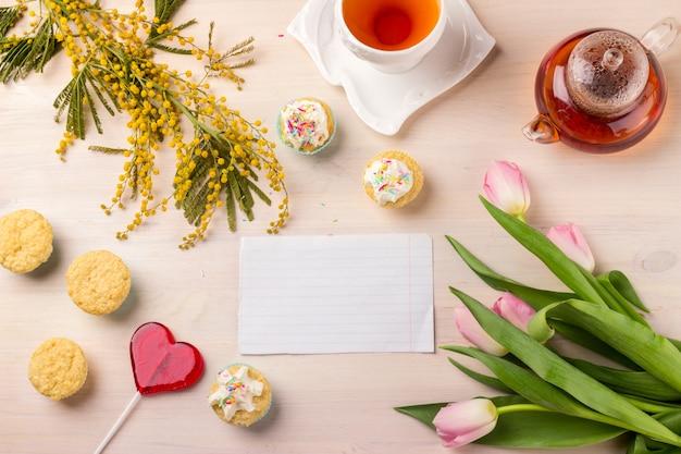 Lente wenskaart met tulpen, mimosa, thee en cakejes op houten tafel. Premium Foto